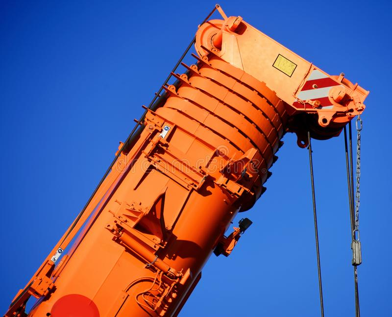 Zoom shot of an orange-coloured truck-mounted crane with telescopic boom pushed together royalty free stock photo