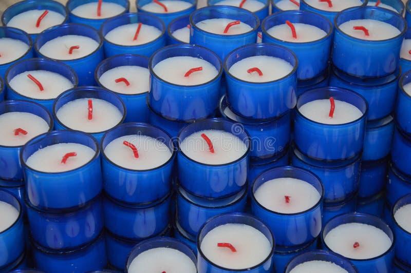 Zooma på blåa Candels i en lilla Chuch royaltyfria foton