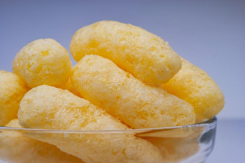 Zoomed Corn Puffs in a Glass Bowl. Crunchy Flavored Puffed Snacks. Party, Movie Snacks royalty free stock photo