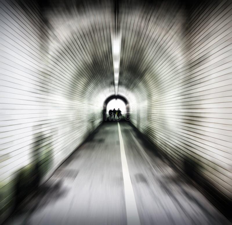 Zoomsuddighetsbild av en gammal mörk fot- tunnel med unidentifiable folk som dyker upp in i ljuset arkivfoto