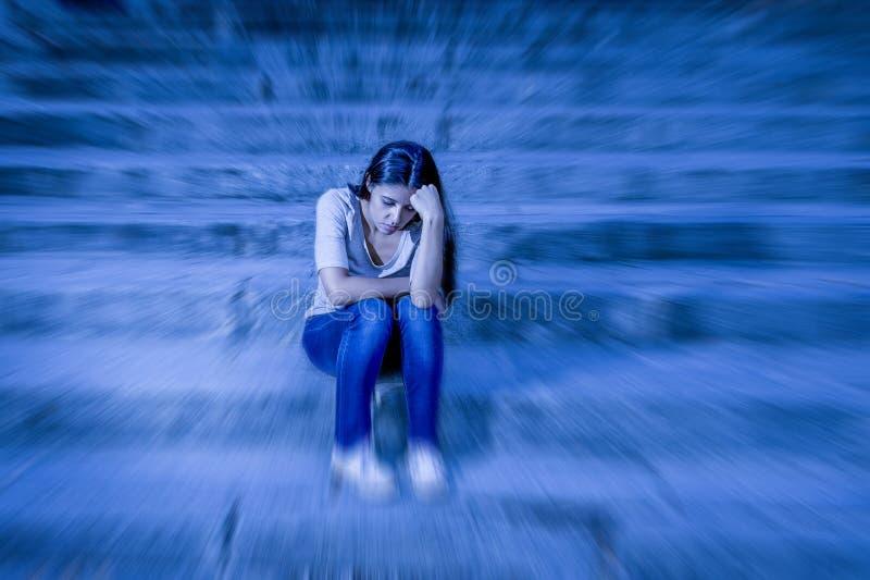 Zoomunschärfe redigierte Porträt der jungen traurigen und deprimierten Frau oder des jugendlich Mädchensitzens, die am Straßentre stockfotografie