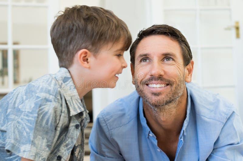 Zoon die aan vader fluisteren stock afbeelding