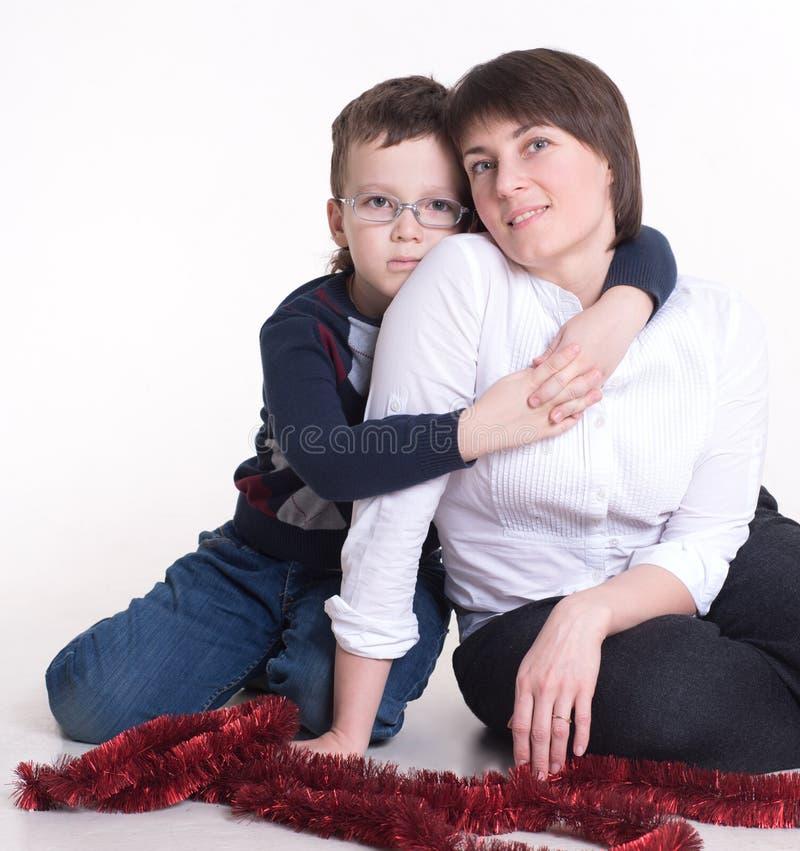 Zoon die in glazen de schouders van haar moeder koesteren royalty-vrije stock foto