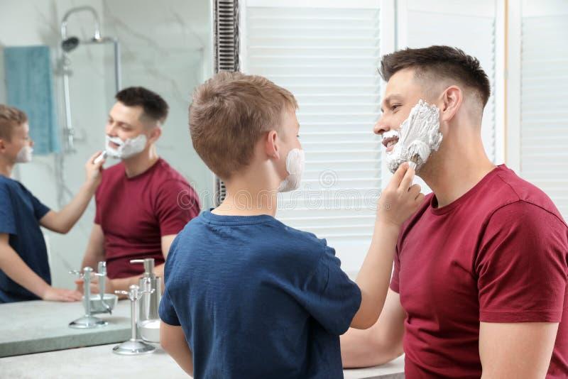 Zoon die het scheren schuim op het gezicht van de papa toepassen bij spiegel stock foto's