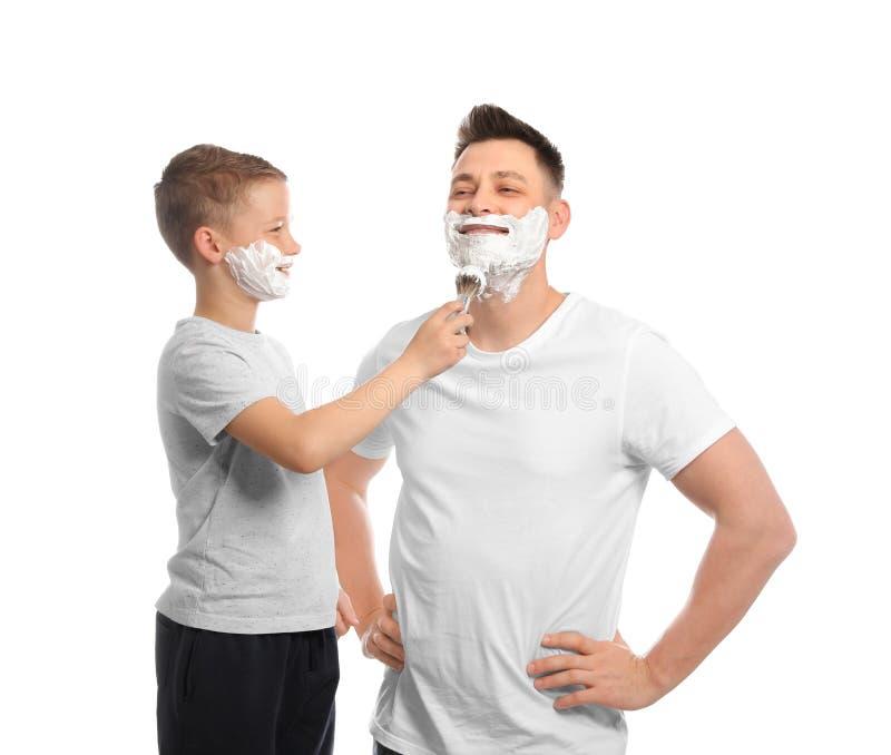 Zoon die het scheren schuim op het gezicht van de papa toepassen stock foto