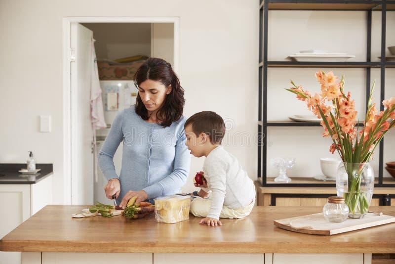 Zoon die Moeder helpen om Voedsel op Keukeneiland voor te bereiden royalty-vrije stock afbeeldingen