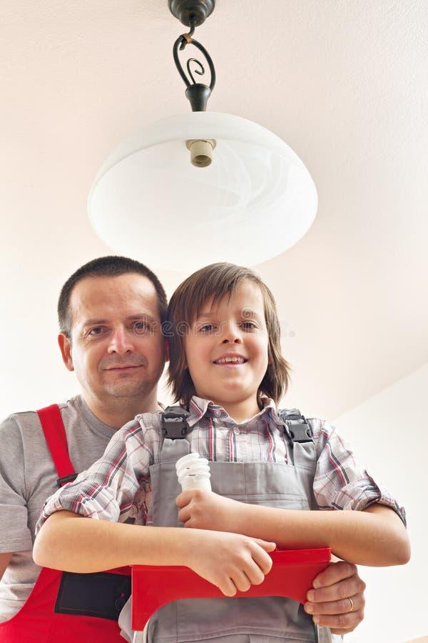 Zoon die vader helpen die een lightbulb veranderen stock afbeeldingen