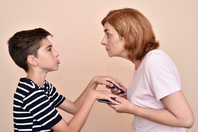 Zoon die zijn moeder niet toestaan om zijn smartphones te controleren stock foto's