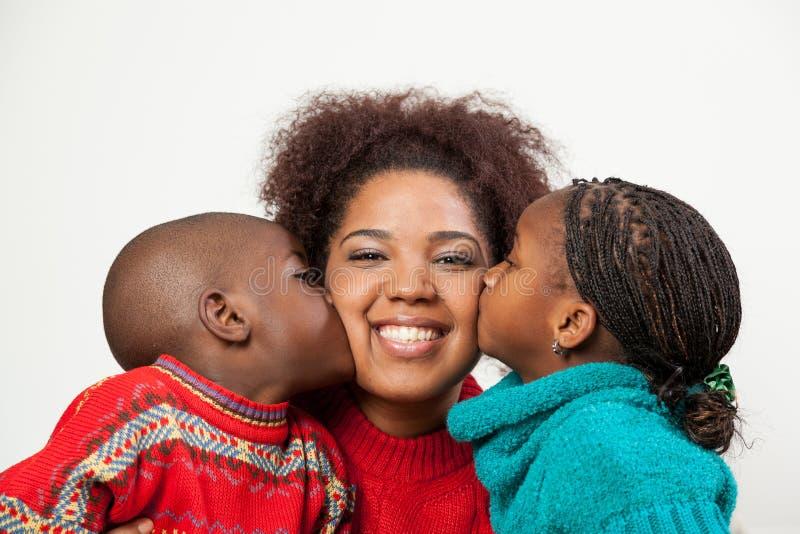 Zoon en dochter die haar moeder kussen royalty-vrije stock foto's