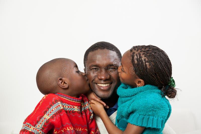 Zoon en dochter die haar vader kussen royalty-vrije stock afbeelding