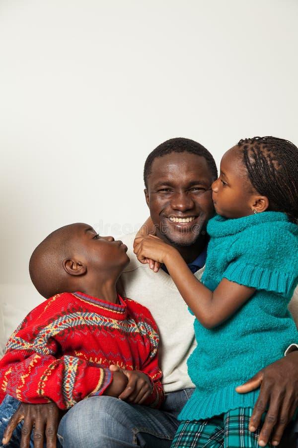 Zoon en dochter die haar vader kussen stock foto's