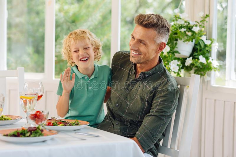 Zoon en papa die terwijl buiten samen het eten van lunch lachen royalty-vrije stock afbeelding