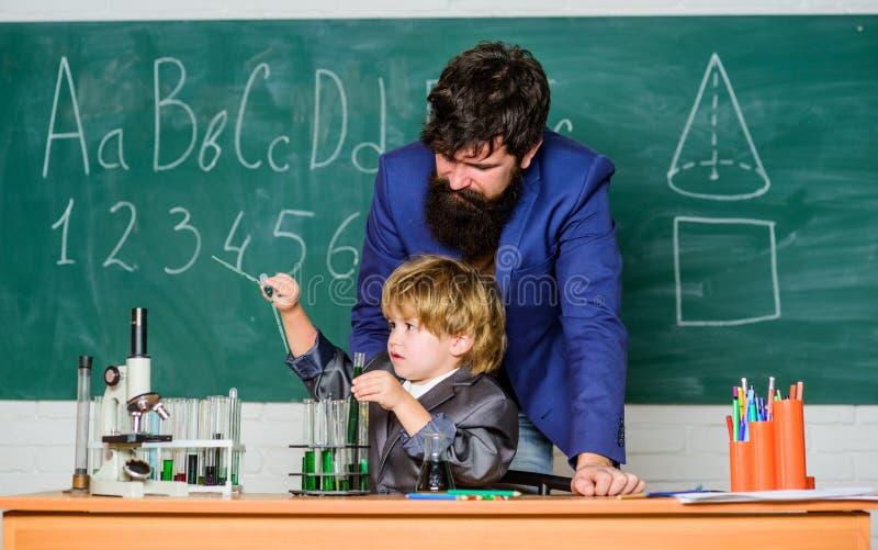 Zoon en vader op school kleine jongen met de leraarsmens wijsheid Terug naar School Apotheek en chemiethema Oplossing binnen royalty-vrije stock foto's