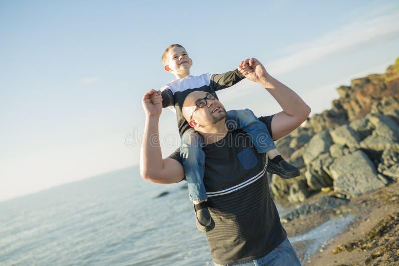 Zoon op vaderschouders bij het strand die pretzonsondergang hebben samen stock foto