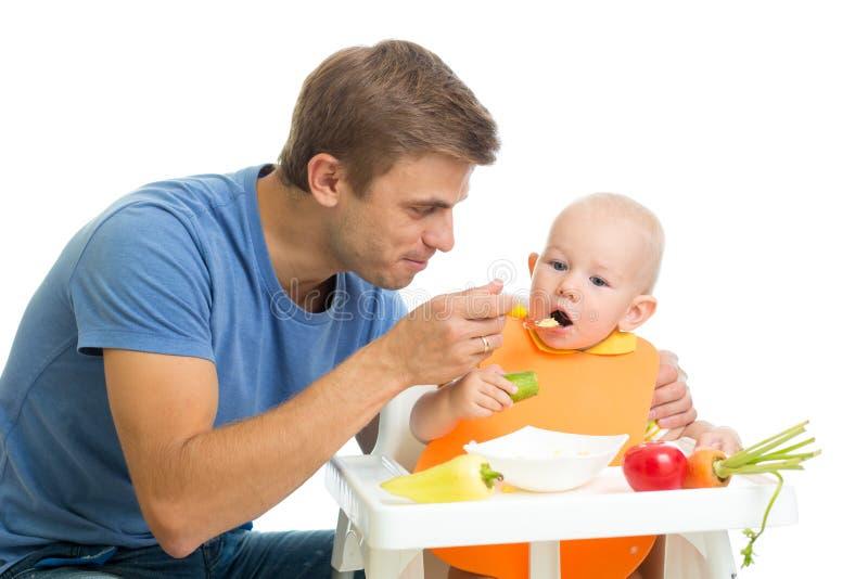 Zoon van de vader de voedende baby door gezond voedsel royalty-vrije stock foto