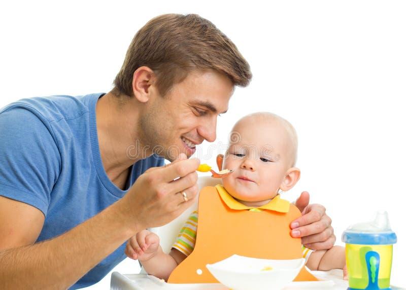 Zoon van de vader de voedende baby door gezond voedsel stock afbeelding