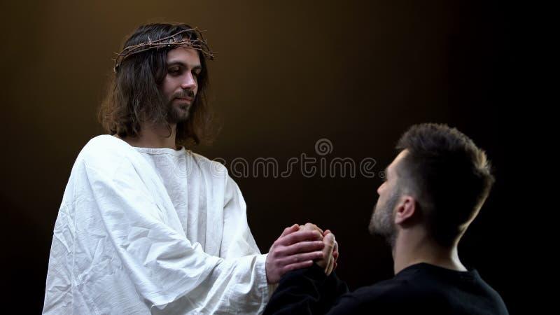 Zoon van God die de handen vasthoudt aan het bidden van de mens, spirituele steun, het verijdelen van zonden royalty-vrije stock afbeeldingen