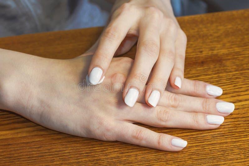 Zorg van vrouwelijke handen met een witte manicure Toepassing van de room royalty-vrije stock foto