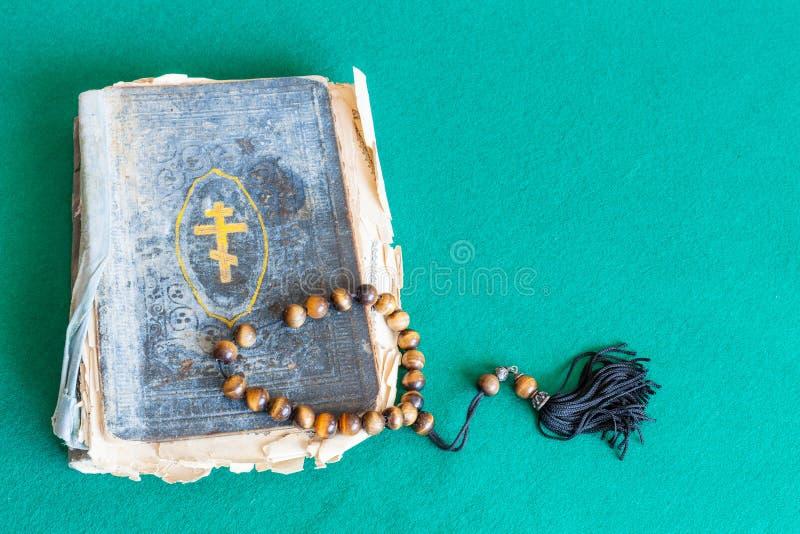 Zorgparels en oud kerkboek op groene lijst royalty-vrije stock foto