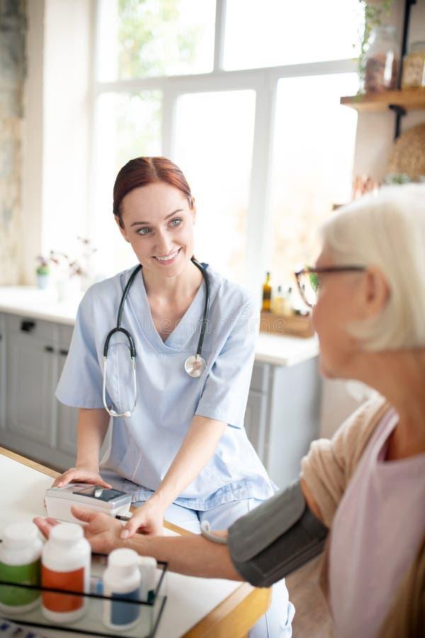 Zorgverlener glimlacht terwijl de druk voor oudere vrouwen wordt gemeten stock afbeeldingen