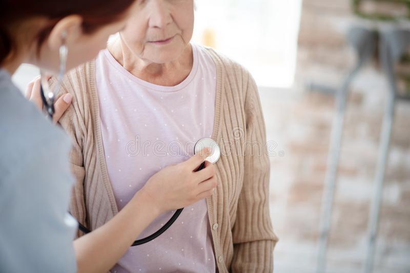 Zorgverpleegkundige die stethoscoop gebruikt terwijl hij gepensioneerde vrouw onderzoekt royalty-vrije stock foto's