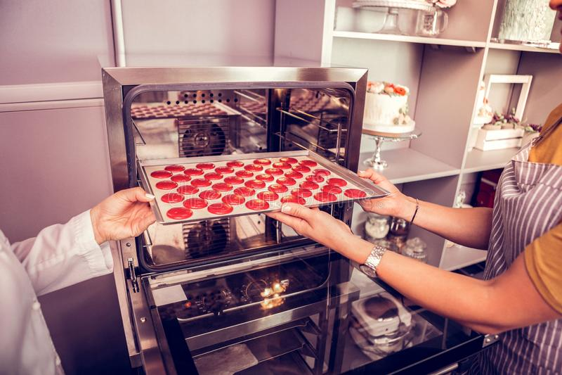 Zorgvuldige jonge banketbakker die gebieden voor macarons voorbereiden royalty-vrije stock afbeelding