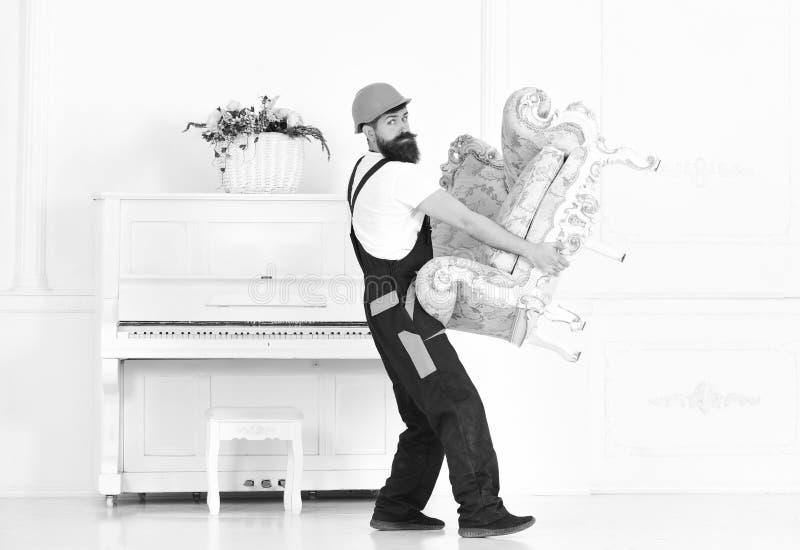 Zorgvuldige verhuizer die antieke leunstoel dragen Arbeider die die voor piano lopen op witte achtergrond wordt geïsoleerd stock foto