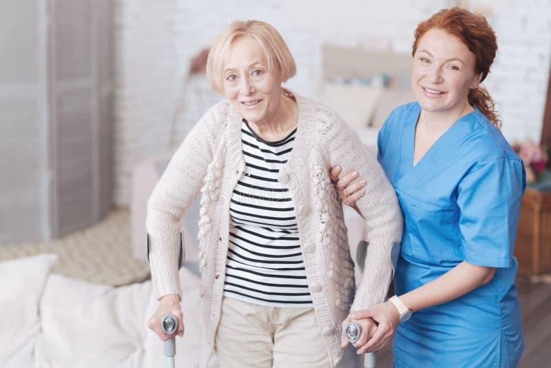 Zorgvuldige vrouwelijke arts die haar bejaarde patiënt helpen te lopen stock foto's