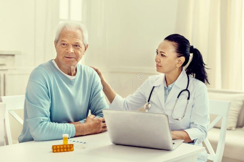 Zorgvuldige vrouwelijke verpleegster die droevige bejaarde patiënt kalmeren royalty-vrije stock fotografie