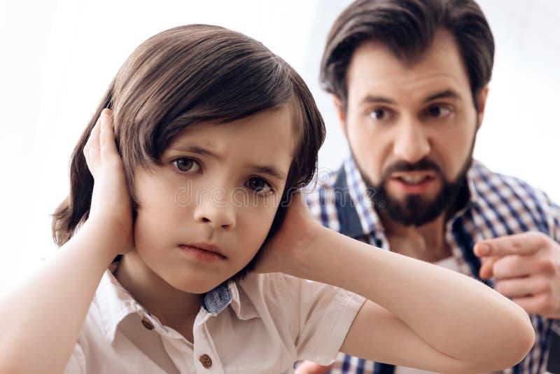 Zorniger Vater schilt jugendlichen Sohn, der Ohren verstopft stockfoto