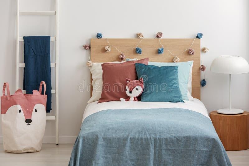 Zorro de la felpa en cama de la chamusquina con las almohadas y el edredón coloridos imagen de archivo libre de regalías