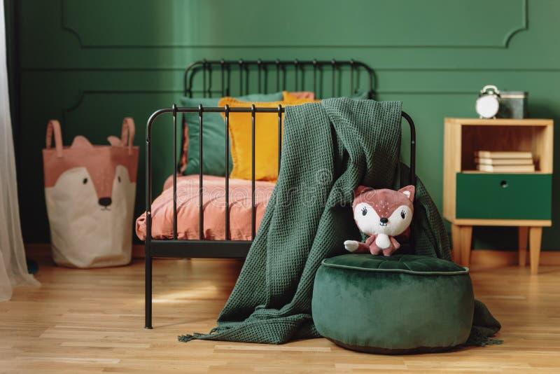 Zorro de la felpa en taburete verde esmeralda del terciopelo en la comida de la sola cama del metal en dormitorio del adolescente imagenes de archivo