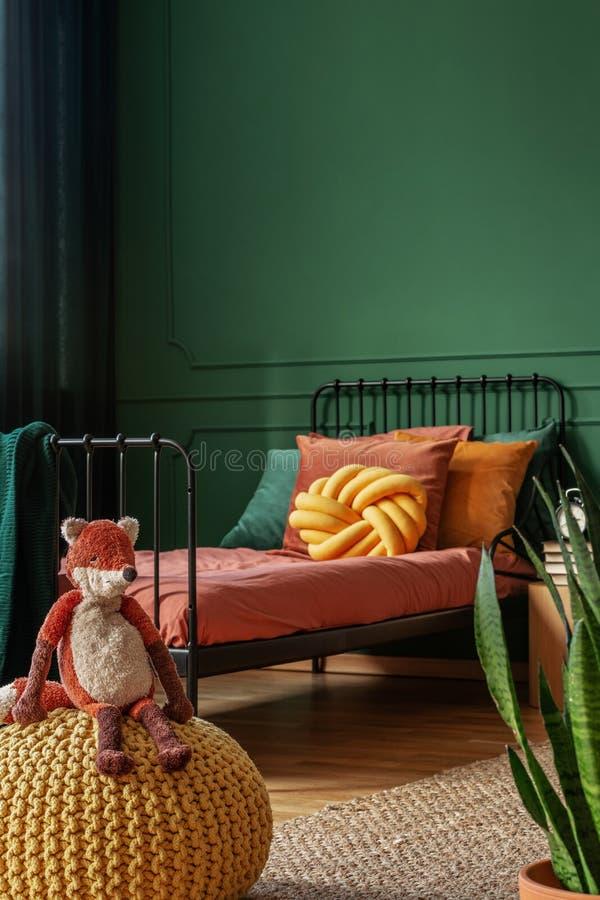Zorro del juguete en un taburete amarillo en una foto real de un dormitorio del niño con las paredes verdes y las hojas anaranjad fotos de archivo