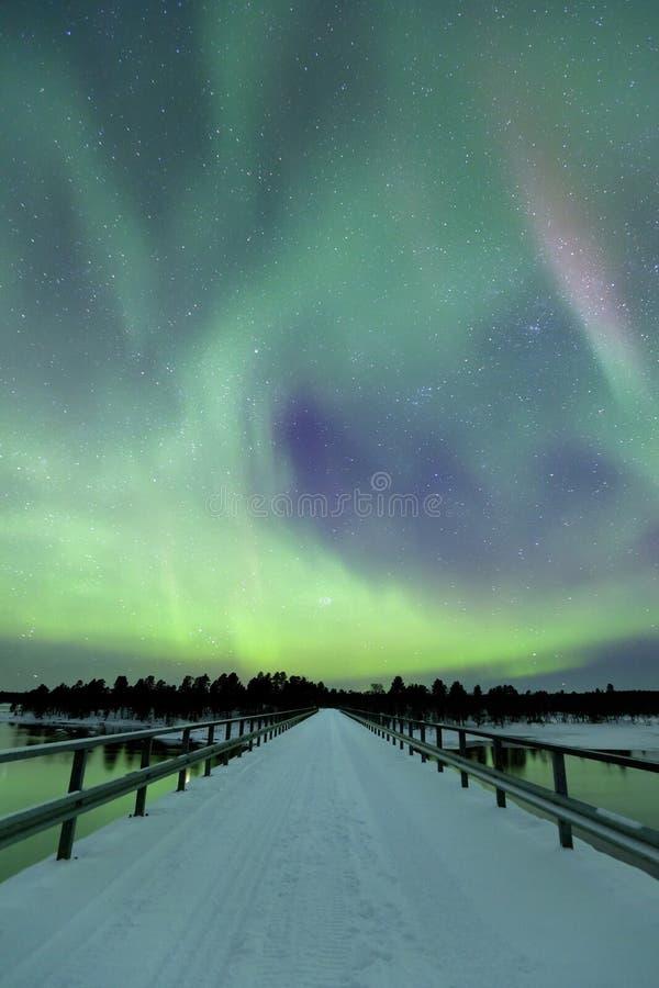 Zorz borealis nad mostem w zimie, Fiński Lapland obrazy royalty free