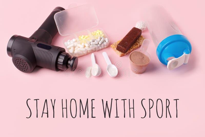 Zostań w domu ze sportem Terapeutyczny perkusyjny pistolet masażowy, posiłek, pigułki, bar sportowy na różowym tle - koncepcja no fotografia stock