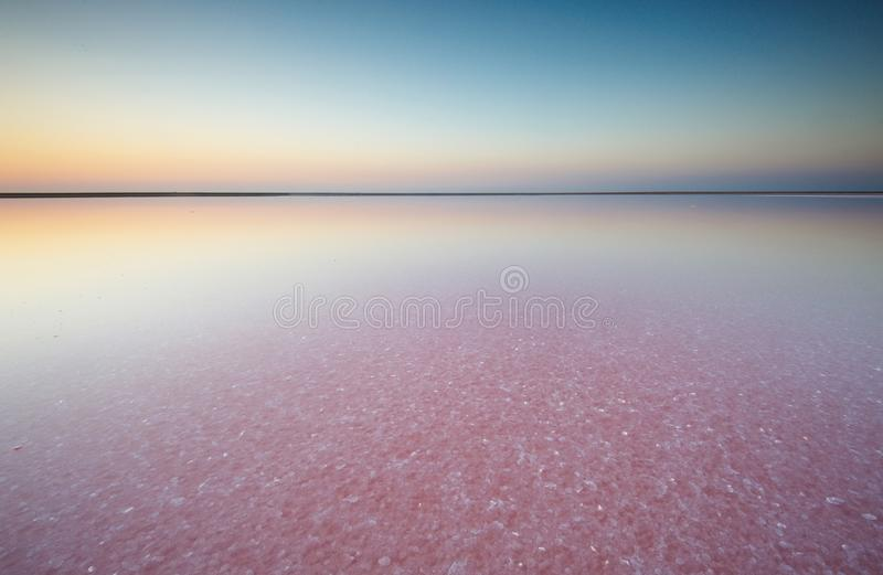 Zout en Pekel van een roze die meer, door het zoutmeer van micro-algendunaliella bij zonsondergang wordt gekleurd stock afbeelding