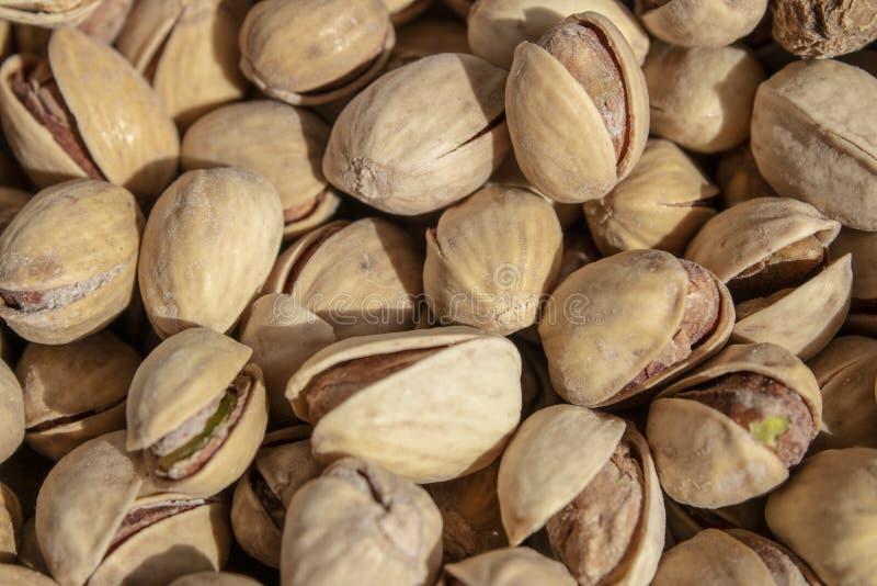 Zoute heerlijke open pistaches in een kom bruine natuurlijke achtergrond van natuurlijke noten stock fotografie