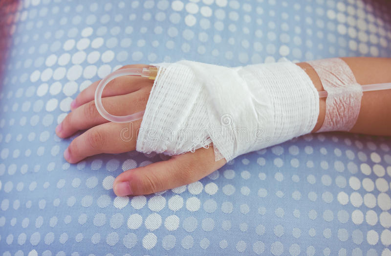 Zoute intraveneuze (iv) druppel in de geduldige hand van een kind stock foto