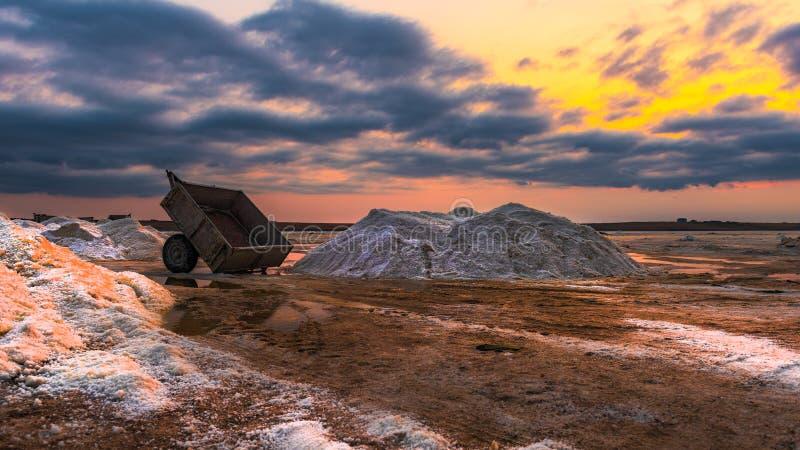 Zoute mijnbouw op droog meer tijdens zonsondergang stock afbeeldingen