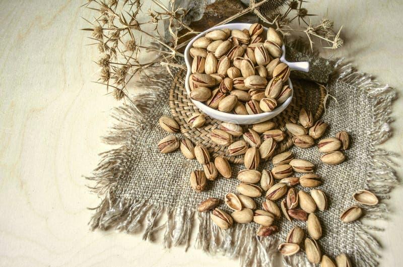 Zoute pistaches in ceramische kop met doornen en marmeren stenen stock foto's