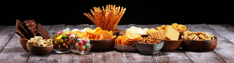 Zoute snacks Pretzels, spaanders, crackers in houten kommen op lijst royalty-vrije stock foto