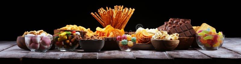Zoute snacks Pretzels, spaanders, crackers in houten kommen op lijst royalty-vrije stock afbeeldingen