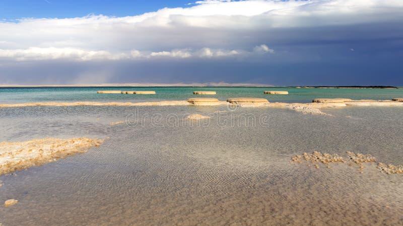 Zoute vormingen in het Dode Overzees van blauwe en turkooise wateren tegen de achtergrond van een stormachtige hemel in wolken stock afbeelding