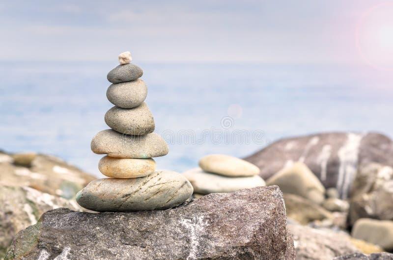 Zrównoważeni kamienie na plaży i słońca świeceniach zdjęcie royalty free