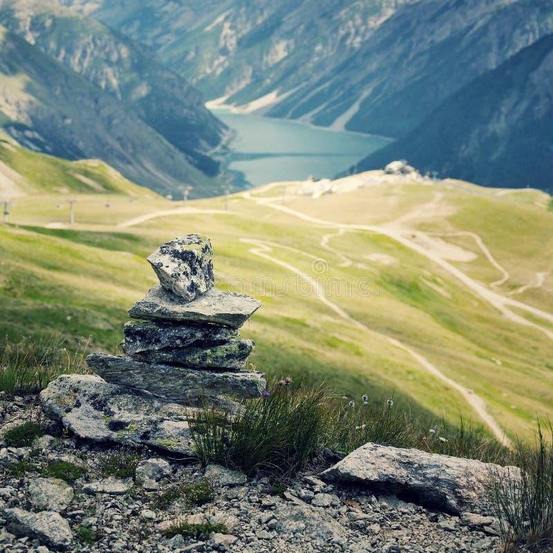 Zrównoważony kamienny ostrosłup z błękitne wody góry jeziorem fotografia stock