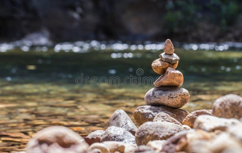 Zrównoważony kamienny pyramide na brzeg Na strumieniu natura Zamazywał tła bokeh fotografia royalty free