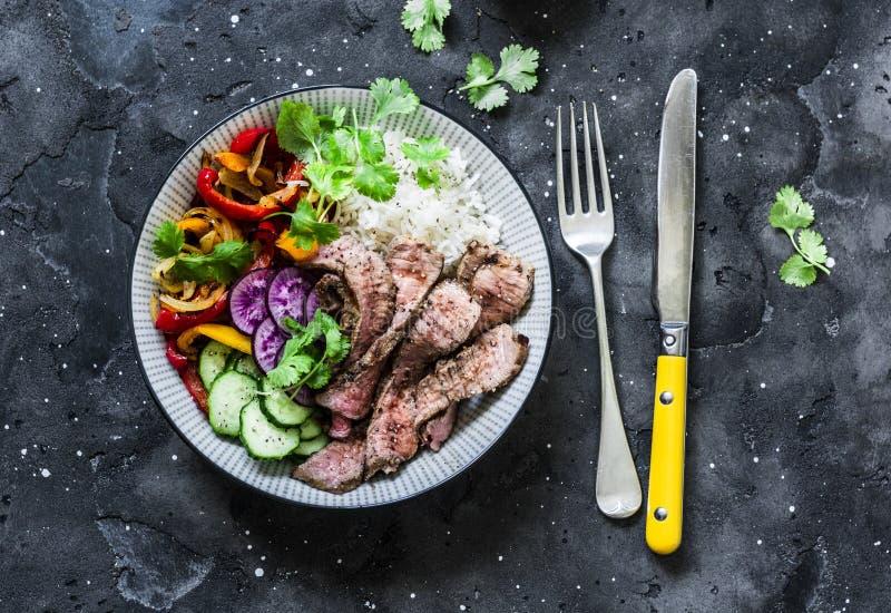 Zrównoważony władzy Buddha puchar - piec na grillu wołowina stku, ryż na ciemnym tle warzywa, piec i świezi, odgórny widok dieta  obrazy stock