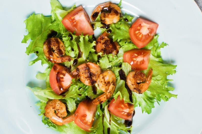 Zr?wnowa?ony zdrowy jedzenie, zielona sa?atka z piec na grillu krewetkami i czere?niowi pomidory pod balsamic, zdjęcia stock