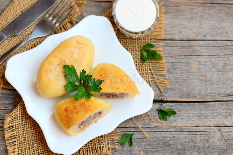 Zrazy fritto della patata farcito con una carne su un piatto bianco Panna acida, forcella, coltello su una tavola di legno d'anna fotografie stock libere da diritti