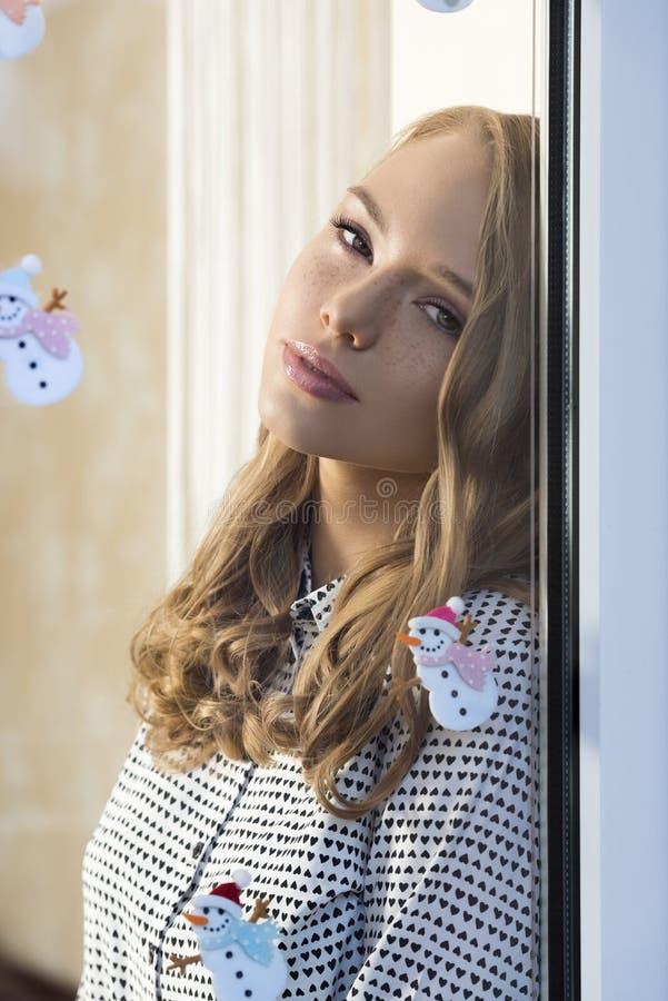 Zrelaksowana dziewczyna przy okno w xmas czasie fotografia royalty free